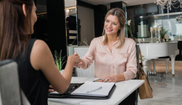 Should Investors Refinance With A Fixed Mortgage Rate? A Woman Shaking Hands With A Mortgage Broker